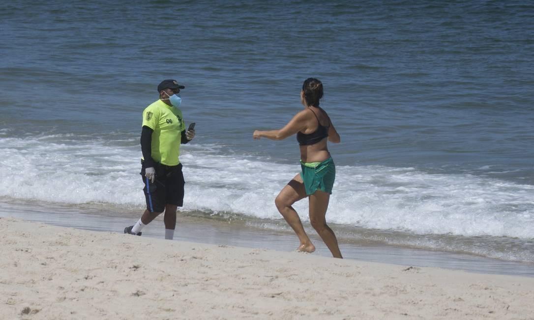 Policial militar retira banhista da praia, no Arpoador Foto: Márcia Foletto / Agência O Globo