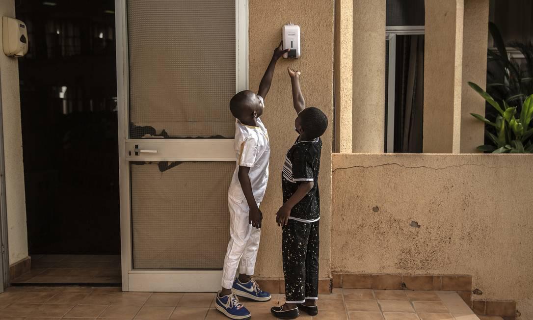 Crianças usam álcool em gel em uma igreja evangélica em Ouagadougou, Burkina Faso Foto: FINBARR O'REILLY / Finbarr O'Reilly/The New York Times