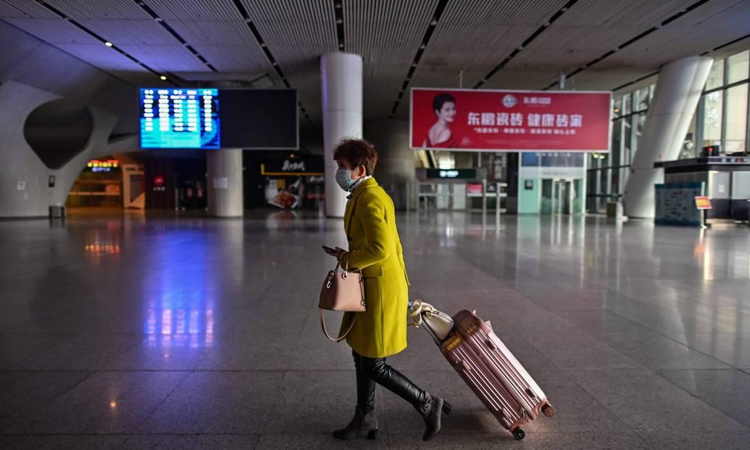 Mulher é vista em estação de trem em Wuhan, após reabertura no sistema ferroviário Foto: HECTOR RETAMAL / AFP