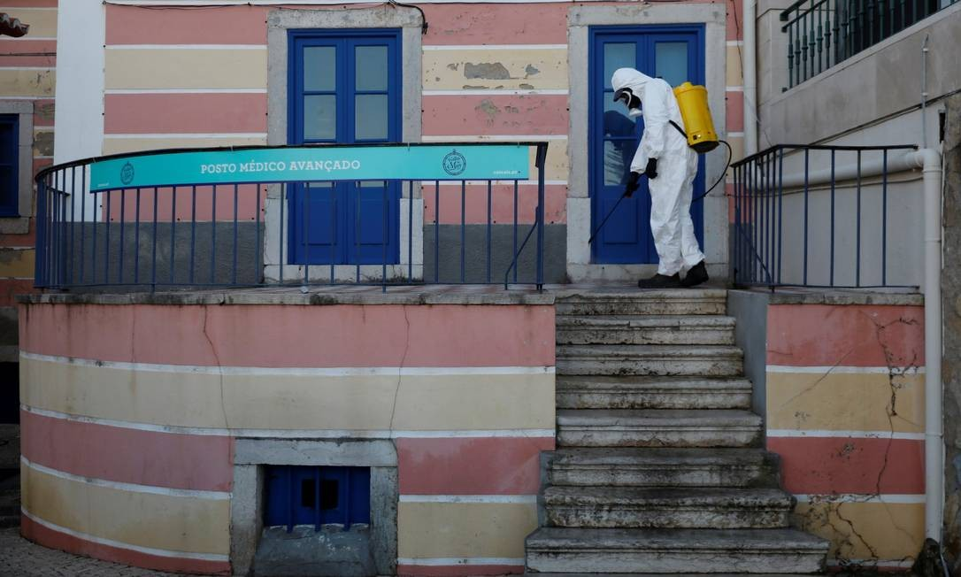 Homem com roupa de proteção desinfecta centro médico em Cascais Foto: RAFAEL MARCHANTE / REUTERS
