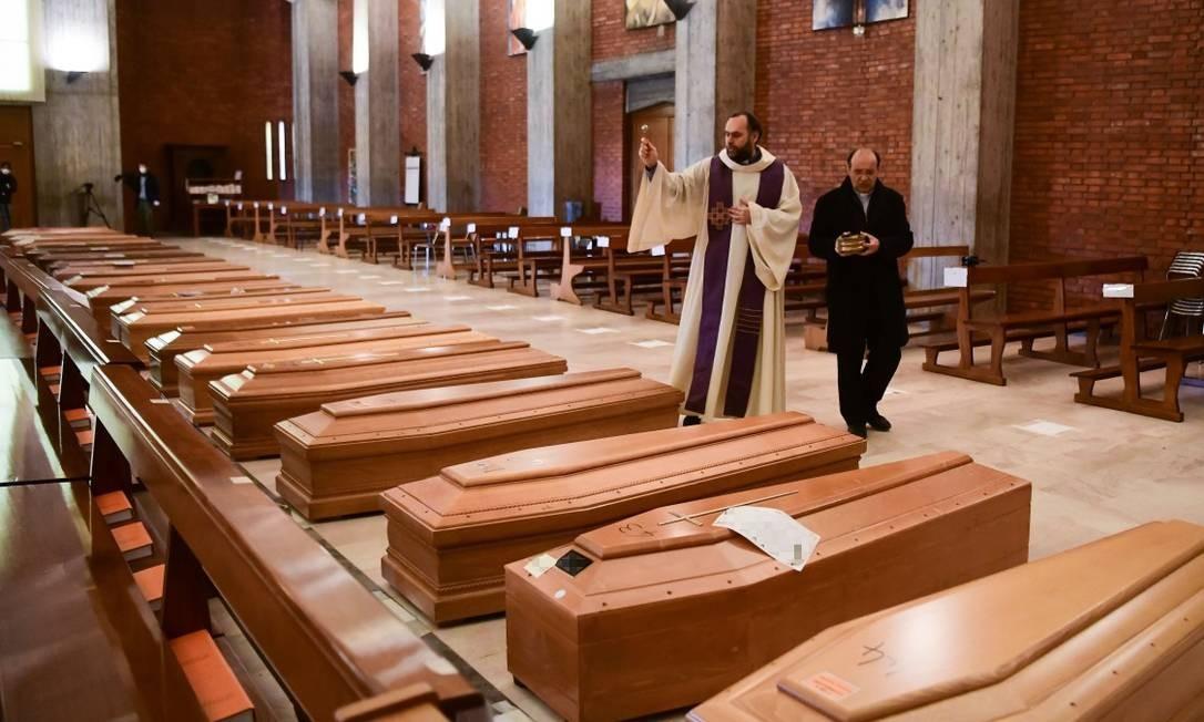 Padre abençoa caixões de mortos por Covid-19 na Itália Foto: PIERO CRUCIATTI / AFP