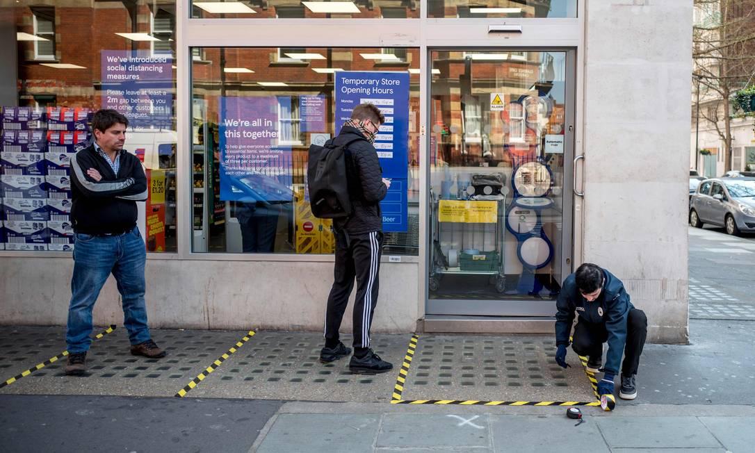 Funcionário de um supermercado marca zonas de distanciamento social para clientes do lado de fora, no centro de Londres Foto: TOLGA AKMEN / AFP
