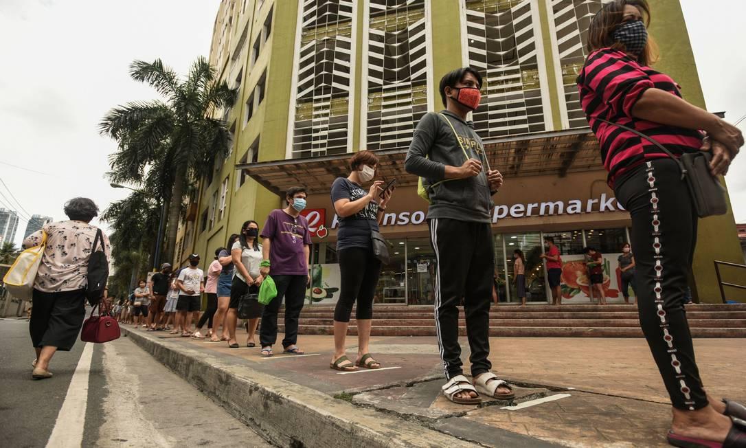 Clientes se distanciam como medidas de distanciamento social, em meio a preocupações com o novo coronavírus, enquanto aguardam do lado de fora de um supermercado em Manila, nas Filipinas Foto: MARIA TAN / AFP