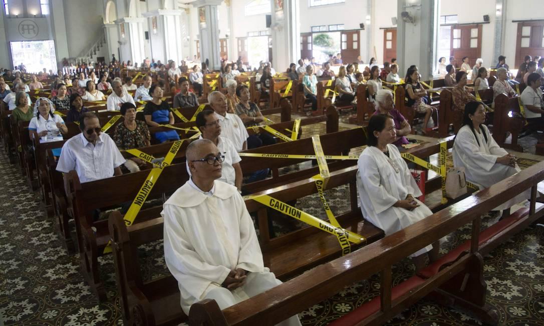 Fiéis católicos sentam-se afastados uns dos outros por fitas que os demarcam os bancos de uma igreja na cidade de Borongan, província de Samar Oriental, centro das Filipinas Foto: ALREN BERONIO / AFP