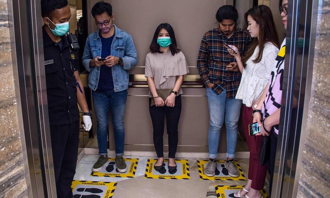 Pessoas ficam em áreas designadas para garantir o distanciamento social dentro de um elevador em um shopping, em Surabaya, na Indonésia Foto: JUNI KRISWANTO / AFP
