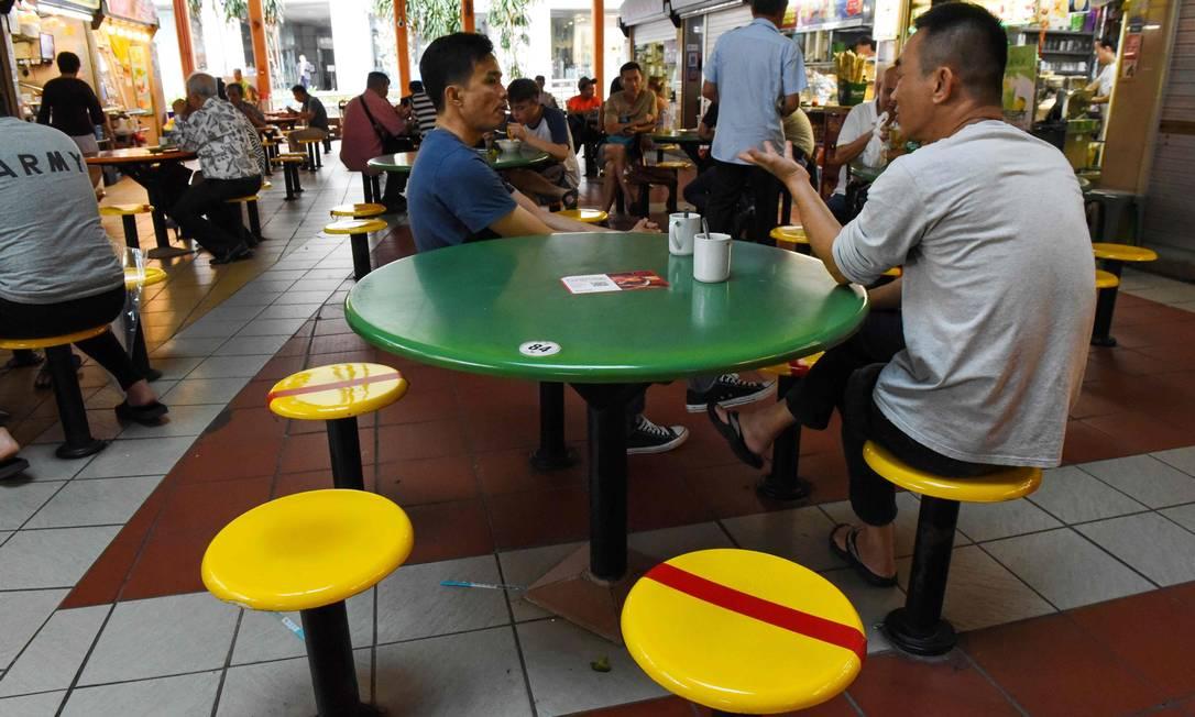 Cadeiras marcadas com fitas vermelhas garantem o distanciamento social entre clientes de um estabelecimento em Cingapura Foto: CATHERINE LAI / AFP