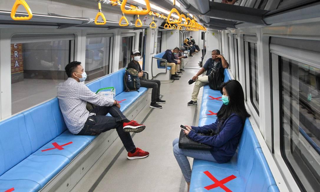 Passageiros sentam-se em áreas designadas para garantir o distanciamento social dentro de um trem leve de trânsito rápido em Palembang, Sumatra do Sul Foto: ABDUL QODIR / AFP