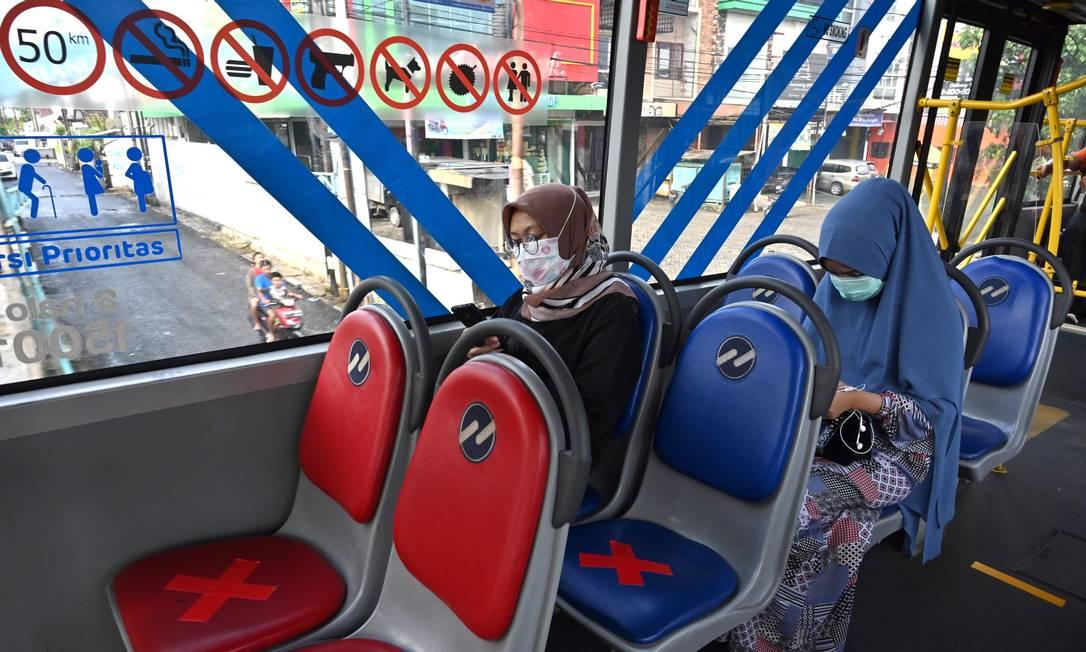 Os passageiros indonésios andam de ônibus com cadeiras designadas para garantir o distanciamento social em Jacarta Foto: ADEK BERRY / AFP
