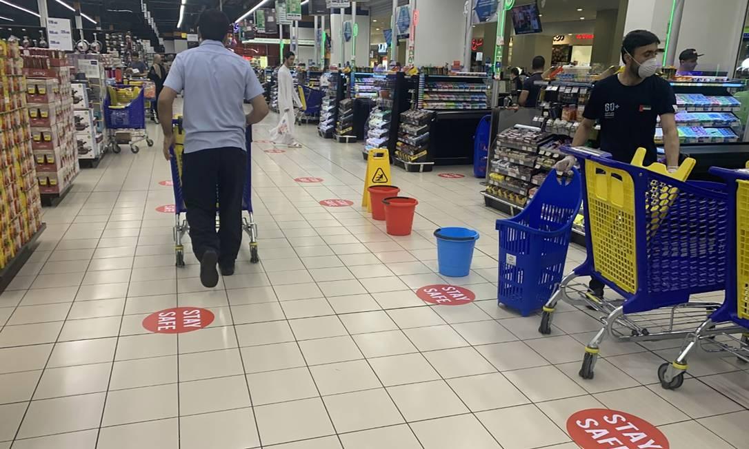Em Dubai, adesivos no chão ajudam a manter distanciamento social entre cliente ao longo dos corredores de um supermercado Foto: KARIM SAHIB / AFP