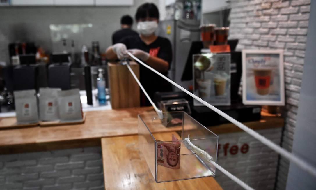 Funcionário de uma cafeteria usa um sistema de roldanas para aceitar dinheiro por uma xícara de café de um cliente, em um esforço para praticar o distanciamento social em meio a preocupações com a propagação do novo coronavírus, em Bangkok Foto: LILLIAN SUWANRUMPHA / AFP