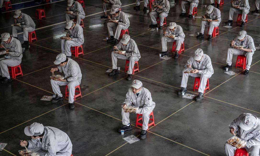 Funcionários comem durante o almoço em uma fábrica de automóveis da Dongfeng Honda, em Wuhan, na província central de Hubei, na China Foto: STR / AFP