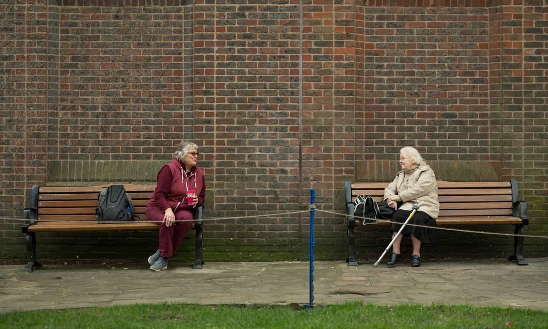 Duas mulheres adotam medidas de distanciamento social enquanto conversam em bancos diferentes de um parque no centro de York, norte da Inglaterra. Por causa da pandemia de Covid-19, pessoas estão reiventando a forma de viver e socializar no mundo Foto: OLI SCARFF / AFP