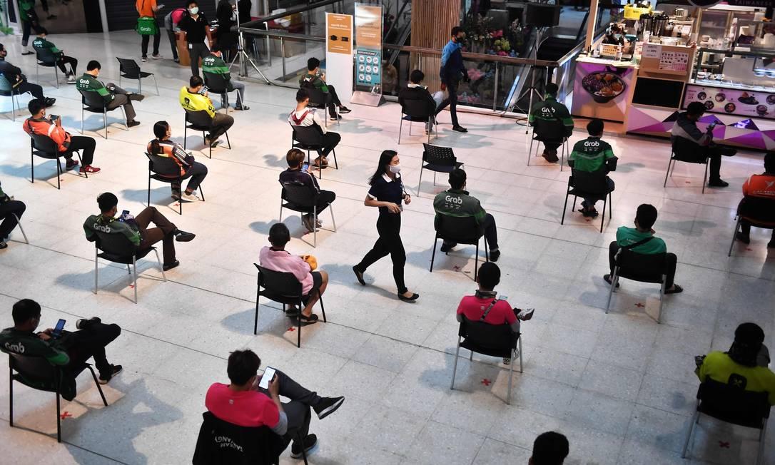 Motoristas e clientes de entrega de alimentos sentam-se em cadeiras espaçadas para distanciamento social enquanto aguardam pedidos para entrega no shopping Central Pinklao, em Bangkok Foto: LILLIAN SUWANRUMPHA / AFP