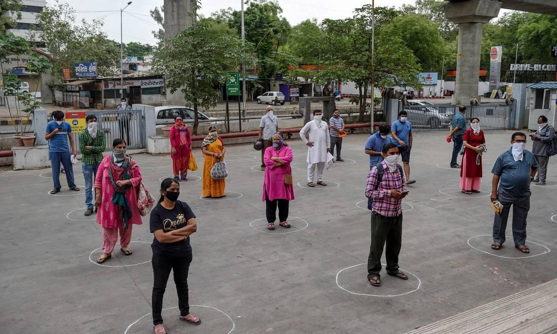 Clientes ficam em círculos marcados no chão para manter a distância social enquanto esperam para entrar no shopping Reliance Mart, em Ahmedabad, na Índia Foto: SAM PANTHAKY / AFP