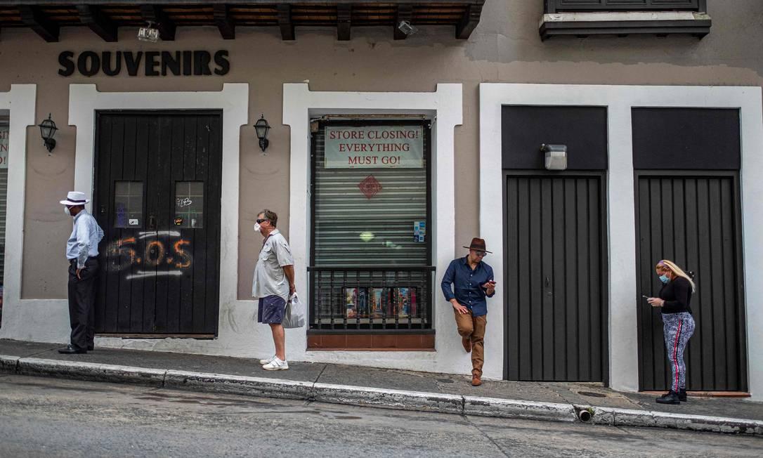 Pessoas fazem fila a uma distância segura para entrar em um supermercado que permite apenas cinco clientes por vez em San Juan, Porto Rico Foto: RICARDO ARDUENGO / AFP