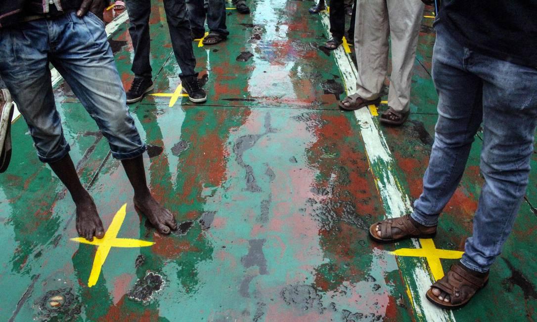 Passageiros ficam sobre marcas amarelas que indicam o distanciamento físico para conter a Covid-19 em uma balsa no terminal de balsas do Likoni, em Mombaça, no Quênia Foto: - / AFP