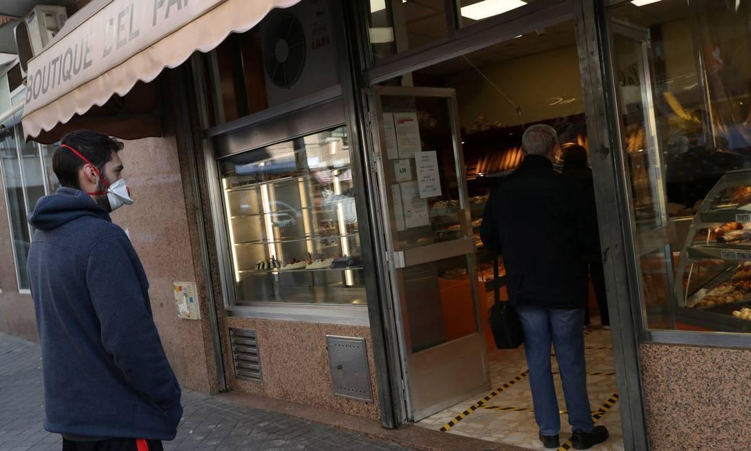 Pessoas praticam distância social enquanto esperam para fazer compras em uma padaria de Madri Foto: SUSANA VERA / REUTERS/29-03-2020