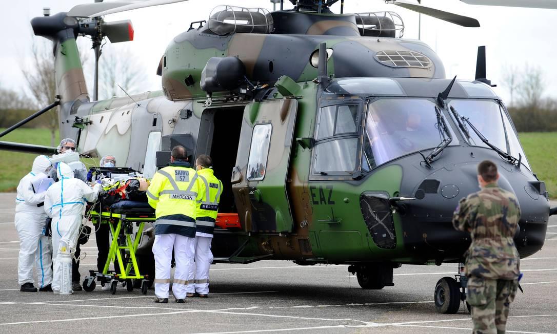 Equipe médica empurra paciente em uma maca em direção a um helicóptero para ser evacuado para um hospital alemão Foto: JEAN-CHRISTOPHE VERHAEGEN / AFP/20-03-2020