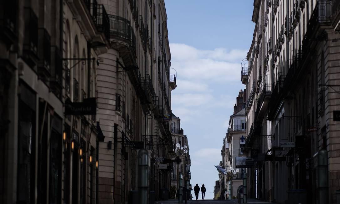 Casal desce uma rua em Nantes, no Oeste da França, no 13º dia de confinamento devido à Covid-19 Foto: LOIC VENANCE / AFP/29-03-2020