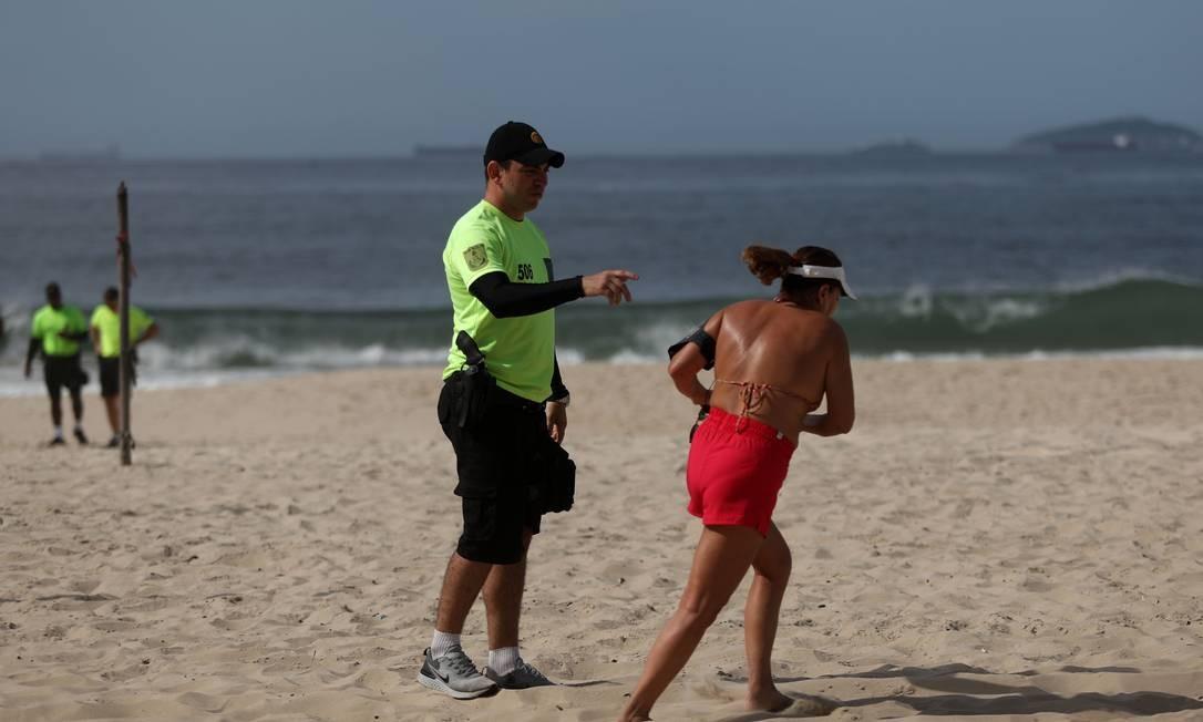 PMs fiscalizam e retiram pessoas da faixa de areia em Copacabana Foto: Fabio Motta / Agência O Globo
