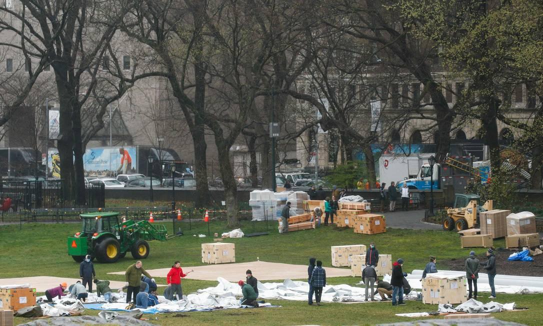 Trabalhadores montam um hospital de campanha no Central Park, em Nova York, cidade mais atingida pelo coronavírus nos EUA Foto: KENA BETANCUR / AFP