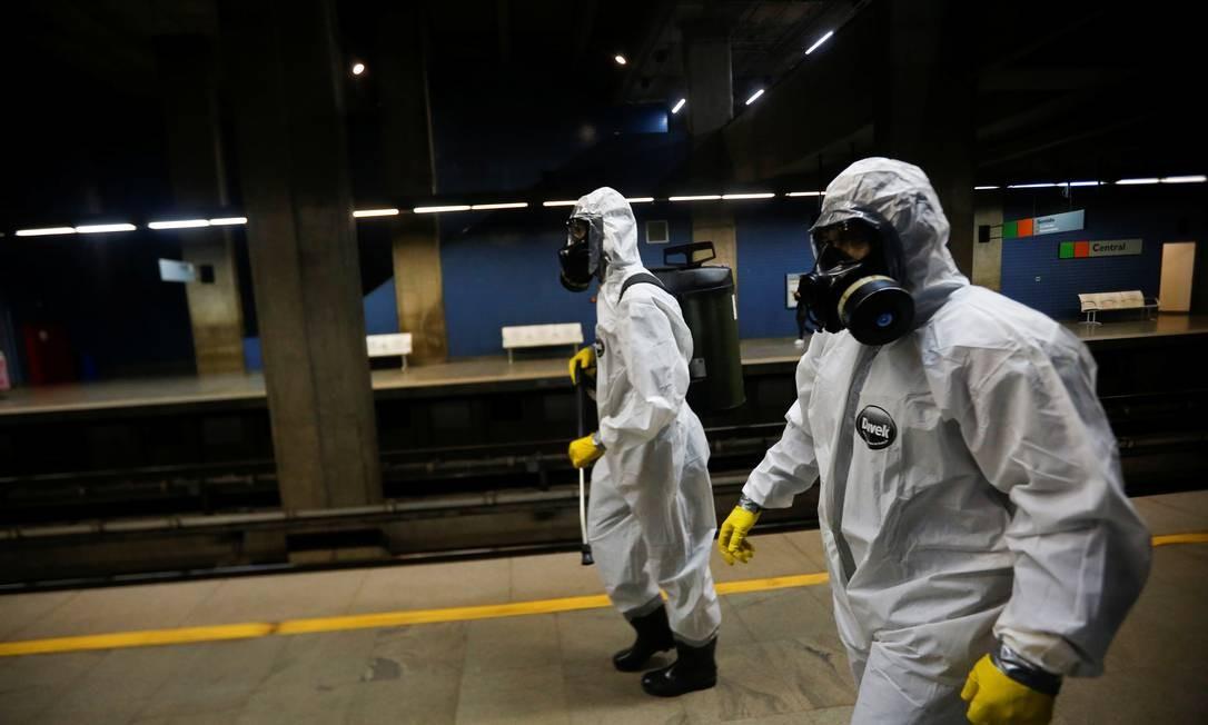 Membros das forças armadas usam roupas de proteção contra a Covid-19 para desinfectar uma estação de metrô em Brasília Foto: ADRIANO MACHADO / REUTERS