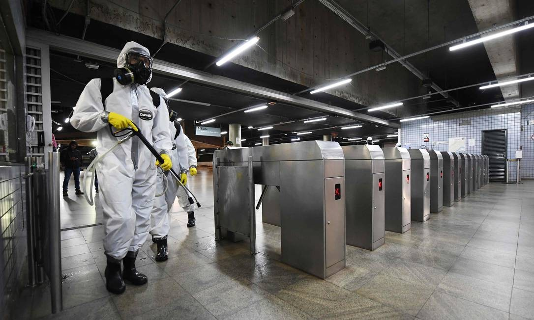 Membros das forças armadas usam roupas de proteção contra o coronavírus para desinfectar uma estação de metrô em Brasília. Foto: EVARISTO SA / AFP