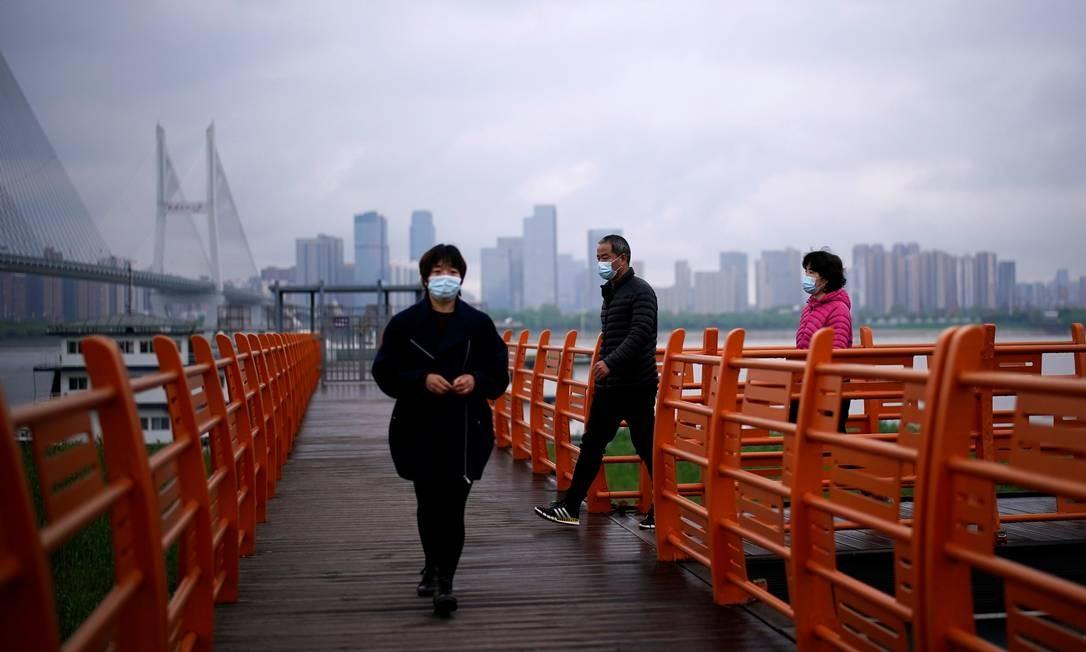 Pessoas andam de máscara pela cidade de Wuhan, capital da província de Hubei, onde a doença começou em dezembro de 2019. Foto: ALY SONG / REUTERS