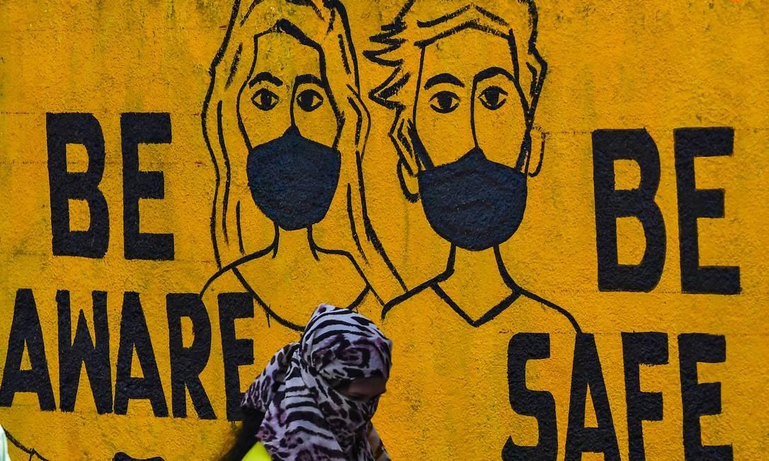 Pedestre cobre rosto com lenço por medo da propagação do coronavírus, em Mumbai, na Índia. Atrás dela, mural com a imagem de duas pessoas usando máscara de proteção e uma mensagem sobre ficar atento e seguro, em meio à pandemia Foto: INDRANIL MUKHERJEE / AFP