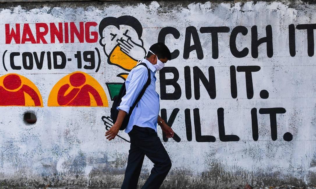 Em outro ponto de Mumbai, na Índia, grafite chama atenção para o perigo da contaminação pelo novo coronavírus Foto: INDRANIL MUKHERJEE / AFP