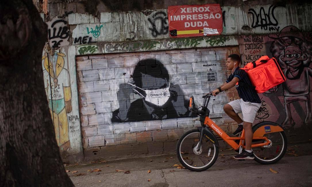 Entregador de bicicleta passa por gravura do presidente do Brasil Jair Bolsonaro na Rua João Paulo I, no Estácio, bairro do Rio de Janeiro. A imagem é referência ao uso desastros da máscara de proteção em coletiva de imprensa, dias após o presidente ter descumprido ordem de isolamento e participado de manifestação com eleitorado Foto: MAURO PIMENTEL / AFP