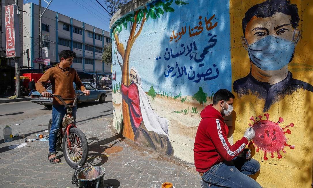"""Artista palestino pinta um mural que diz: """"Ao combater a epidemia, protegemos o ser humano e preservamos a terra"""", em Rafah, no sul da Faixa de Gaza Foto: MOHAMMED ABED / AFP"""