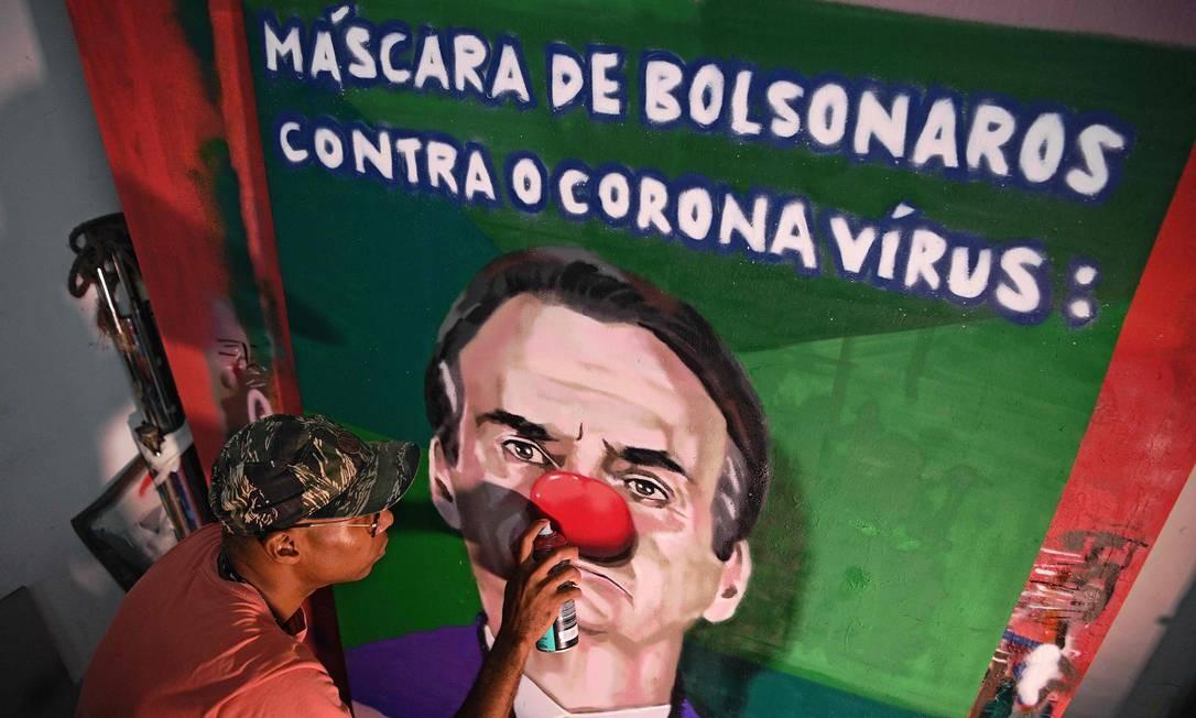 Grafiteiro brasileiro Aira Ocrespo termina uma obra de arte com o presidente Jair Bolsonaro. Crítica surge após a mesma coletiva de imprensa, do dia 18 de março Foto: CARL DE SOUZA / AFP