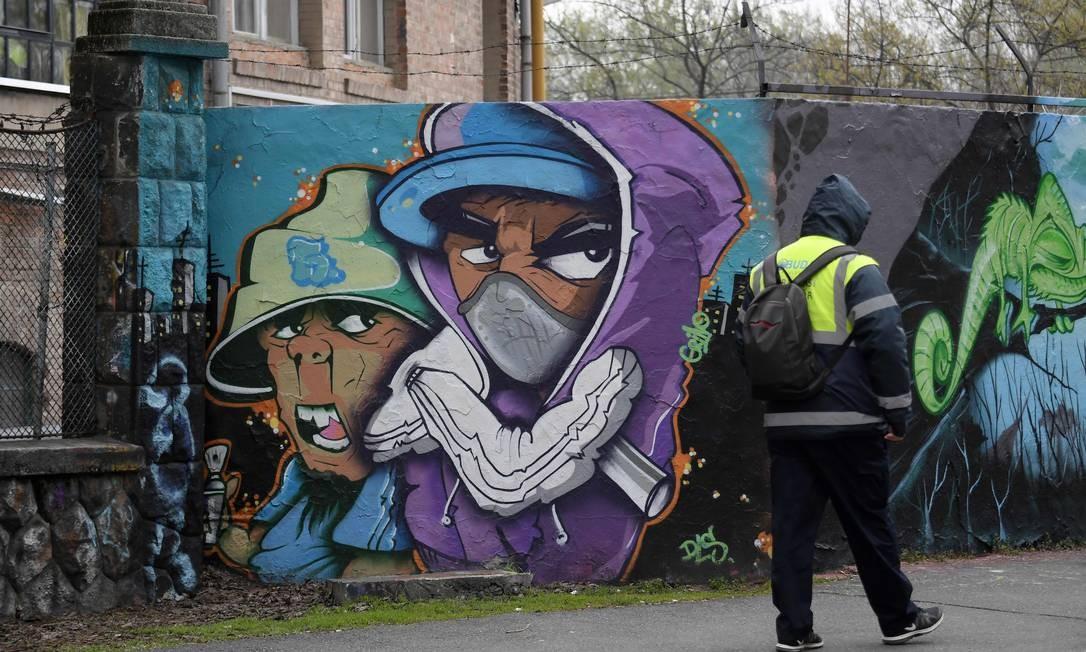 """Grafite mostra um personagem com uma máscara facial perto do local onde o Festival da Ilha """"Sziget"""", na Ilha do Estaleiro, em Budapeste, capital da Hungria Foto: ATTILA KISBENEDEK / AFP"""
