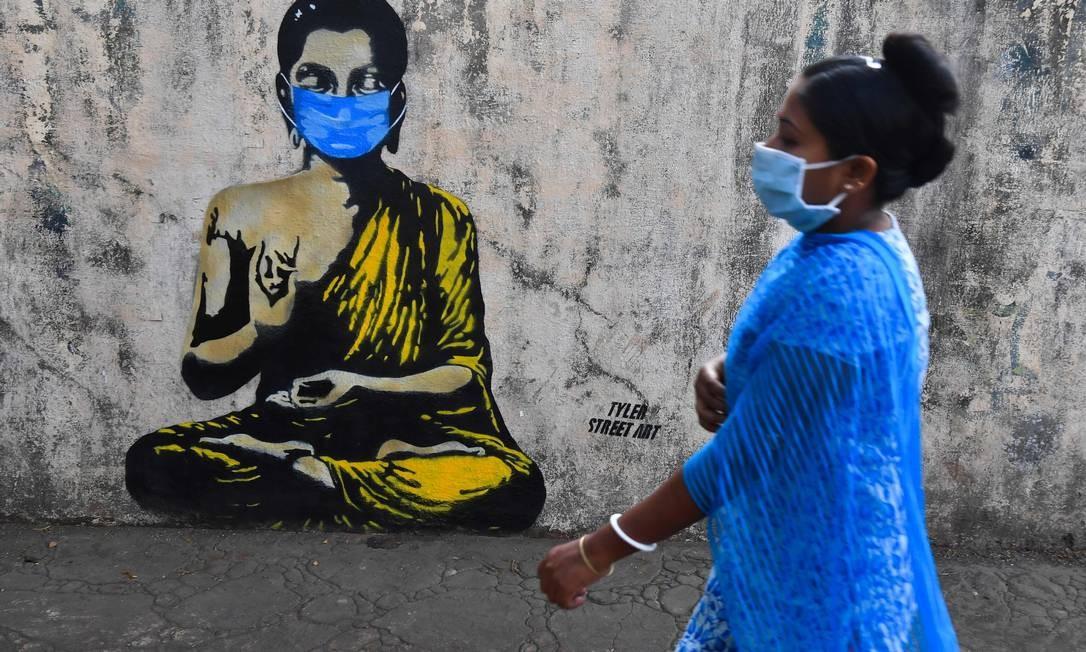Mulher, usando mascara de proteção, passa por grafite com a imagem de Sidarta Gautama – lê-se buda –, também usando máscara, em referência à pandemia do novo coronavírus, em Mumbai, na Índia Foto: INDRANIL MUKHERJEE / AFP