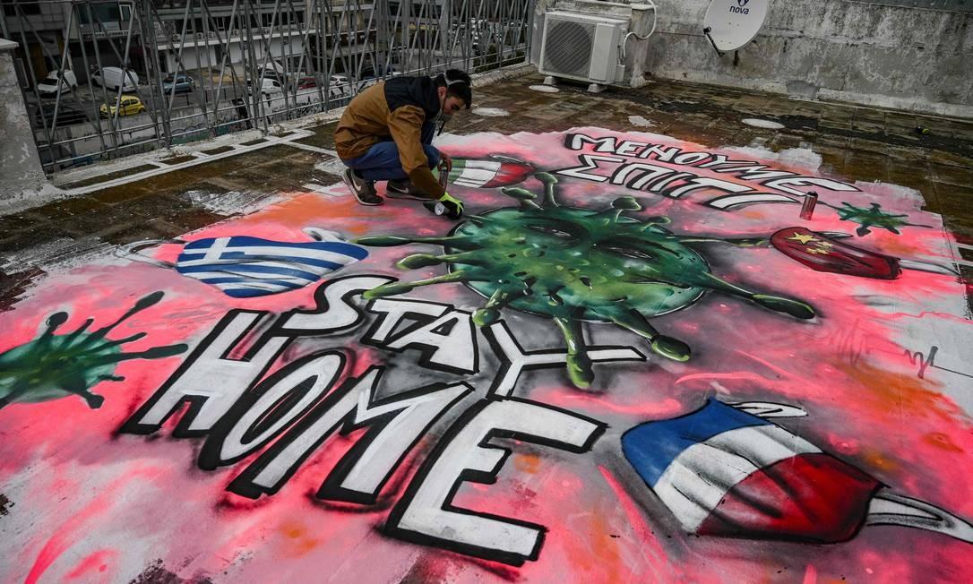 """Grafiteiro de 16 anos finaliza arte com a ilustração de um vírus e a mensagem """"fique em casa"""", escrita em inglês e grego, no terraço do prédio onde vive em Atenas, Grécia. O detenho também conta com bandeiras da Itália, França e China, que lideram número de casos, além do país de onde é nativo – os EUA são o atual epicentro da pandemia Foto: ARIS MESSINIS / AFP"""