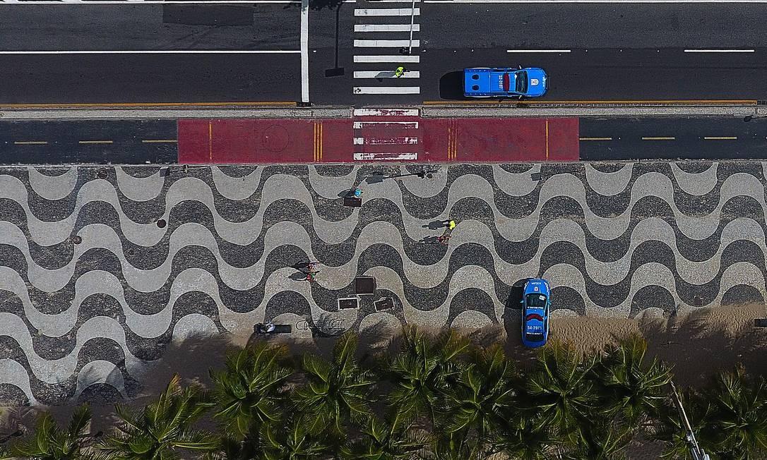 Carros da PM na orla da Zona Sul do Rio: ida à praia continua proibida no estado para evitar propagação do coronavírus Foto: Fabio Motta em 29/03/20 / Agência O Globo
