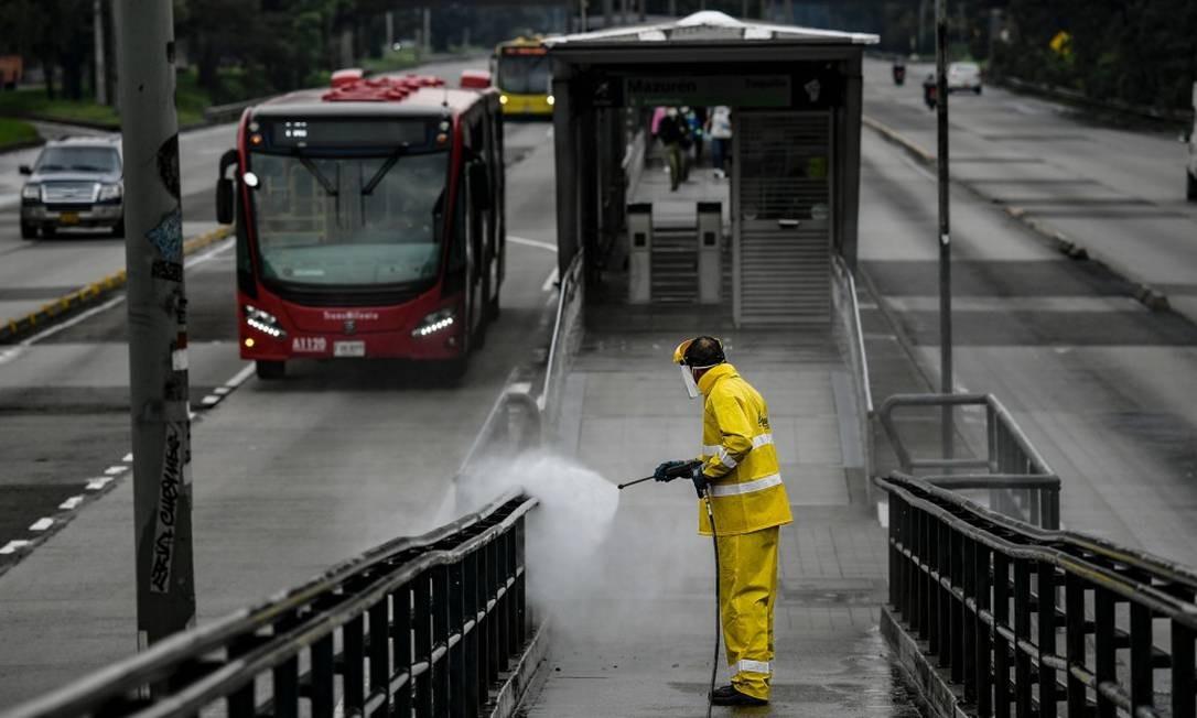 Homem desinfeta ponto de ônibus em Bogotá Foto: JUAN BARRETO / AFP / 28-03-2020