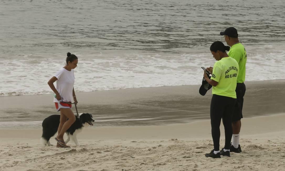 Policiais militares pedem para banhistas deixar a areia na Praia de Copacabana Foto: Gabriel de Paiva / Agência O Globo