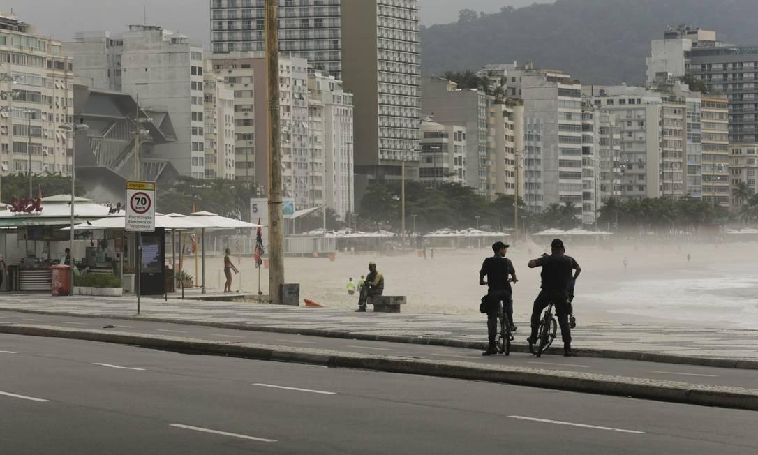 Policiais fazem ronda de bicicleta na praia de Copacabana, na altura do posto 6 Foto: Gabriel de Paiva / Agência O Globo