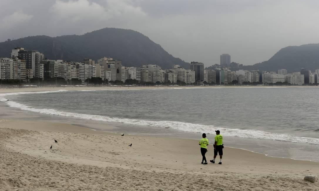 Dois policiais fiscalizam a faixa de areia em Copacabana. Acesso às praias foi proibido por decretos estadual e municipal Foto: Gabriel de Paiva / Agência O Globo