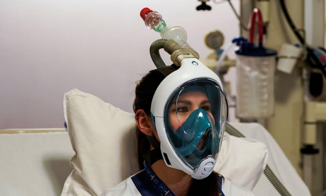 Enfermeira testa uma máscara de mergulho adaptada com acessórios para válvulas respiratórias impressas em 3D. Diante da sobrecarga nos hospitais de vítimas do novo coronavírus que precisam de respiração artificial, profissionais da saúde estão adaptando máscaras de mergulho para aliviar os pulmões dos pacientes Foto: KENZO TRIBOUILLARD / AFP