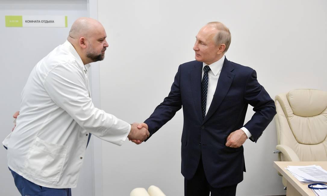 O presidente russo, Vladimir Putin, aperta a mão do médico Denis Protsenko durante visita a um hospital de pacientes de coronavírus Foto: SPUTNIK / via REUTERS/24-03-2020