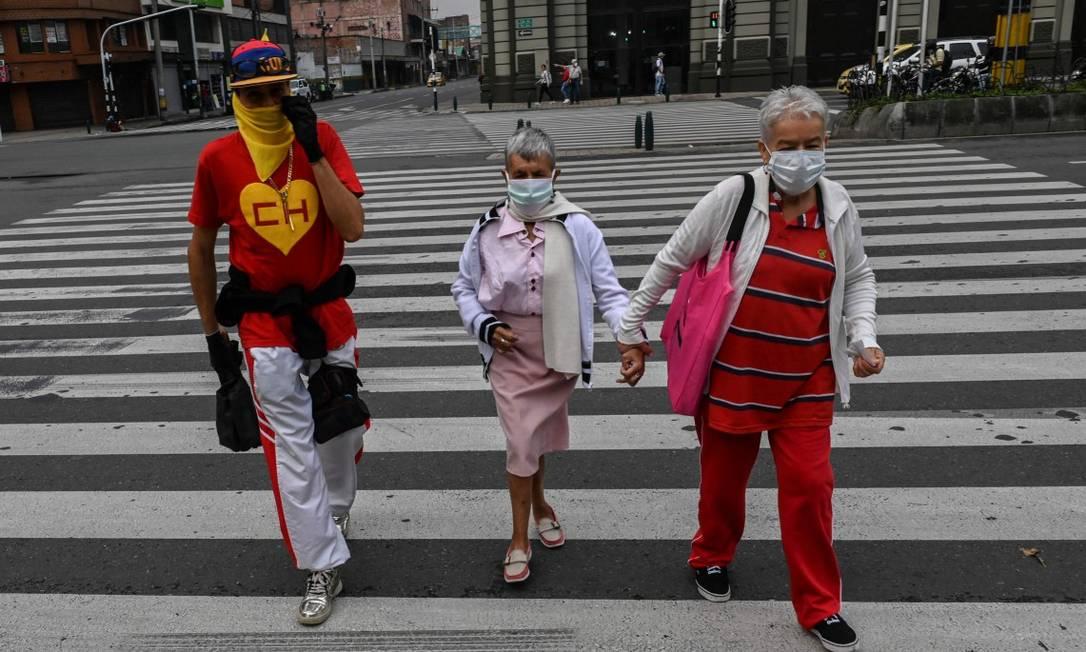 Em Medelín, na Colômbia, pedestres caminham de máscaras Foto: JOAQUIN SARMIENTO / AFP / 30-03-2020