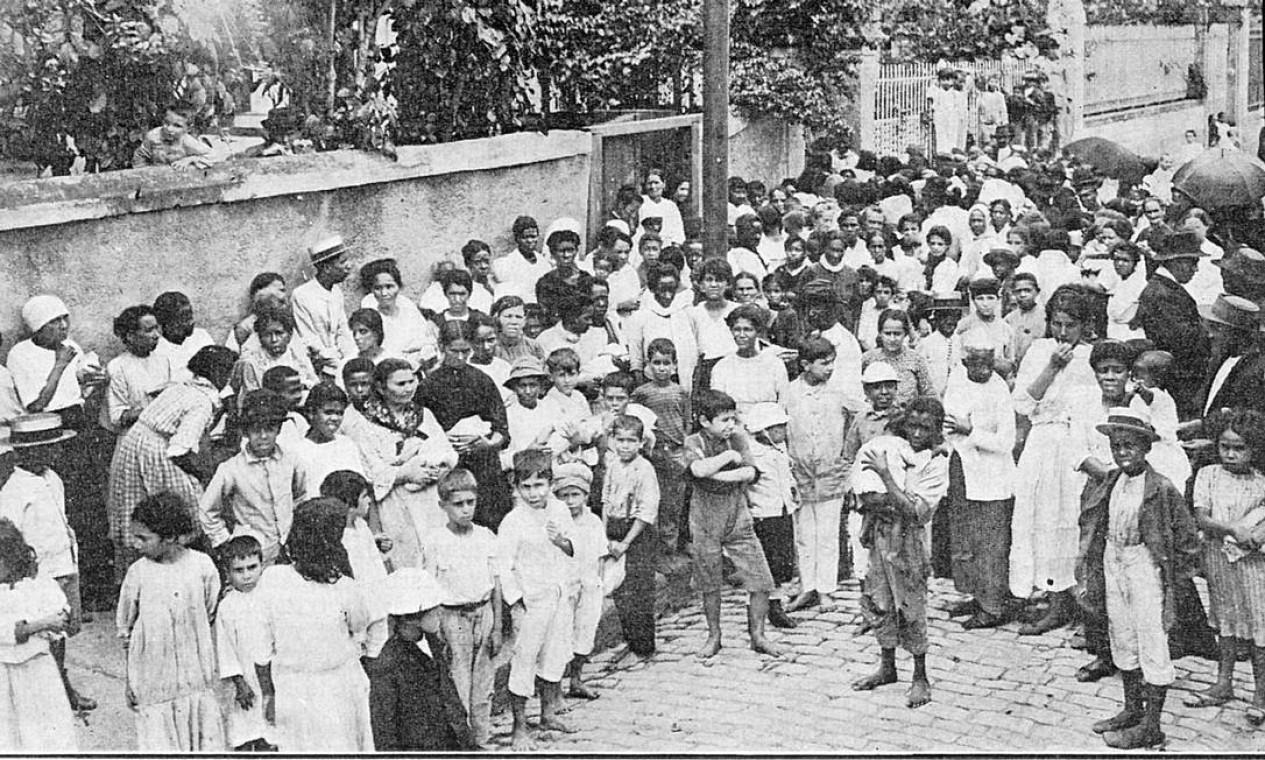"""Gripe espanhola no Rio, em 1918. Legenda da foto diz """"multidão de pobres aguardando socorros"""". Mais de cem anos depois, governos de todo o planeta adotam medidas parecidas para conter uma pandemia que pode contaminar uma parte considerável da população global e paralisar a economia internacional Foto: Reprodução"""