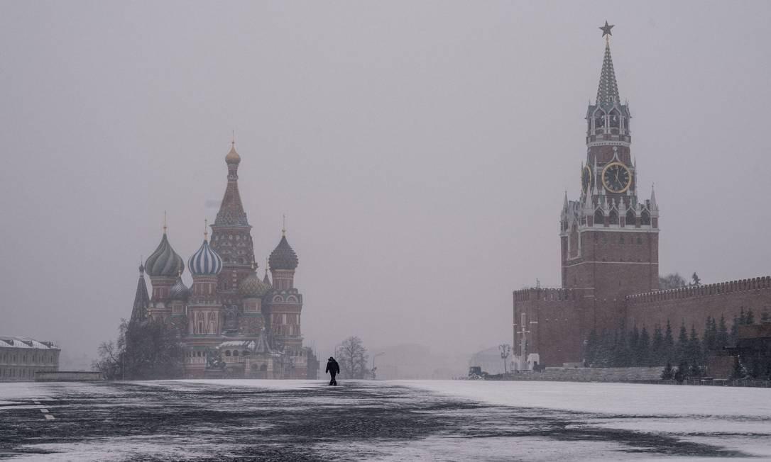 Homem percorre a Praça Vermelha deserta, com a Catedral de São Basílio e a Torre Spasskaya do Kremlin ao fundo, em Moscou Foto: DIMITAR DILKOFF / AFP