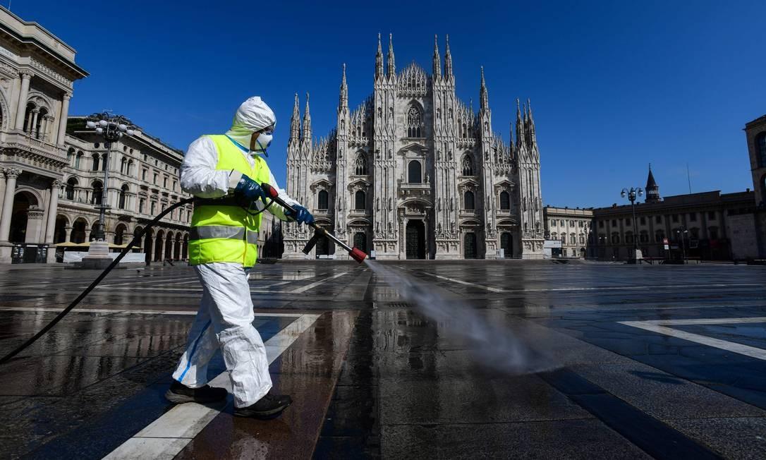 Funcionário de uma empresa de serviços ambientais pulveriza desinfetante na Piazza Duomo, em Milão, com o objetivo de conter a propagação da infecção por Covid-19 Foto: PIERO CRUCIATTI / AFP