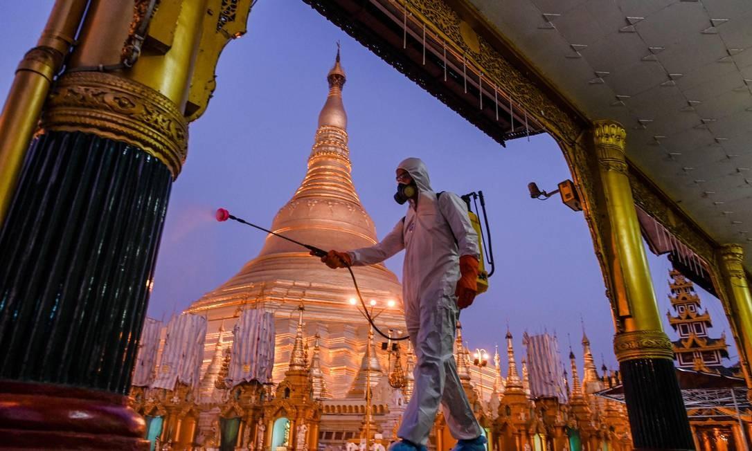Voluntário pulveriza desinfetante no composto do pagode Shwedagon como medida preventiva contra o coronavírus COVID-19, em Yangon. Mianmar relatou sua primeira morte por coronavírus - um homem de 69 anos que voltou ao país em meados de março, depois de receber tratamento contra o câncer na Austrália Foto: YE AUNG THU / AFP