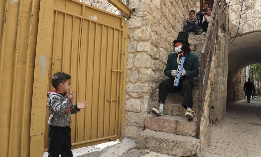 Um artista palestino toca música vestido de palhaço do lado de fora das casas das famílias palestinas, mantendo o confinamento na cidade dividida de Hebron, na Cisjordânia Foto: HAZEM BADER / AFP
