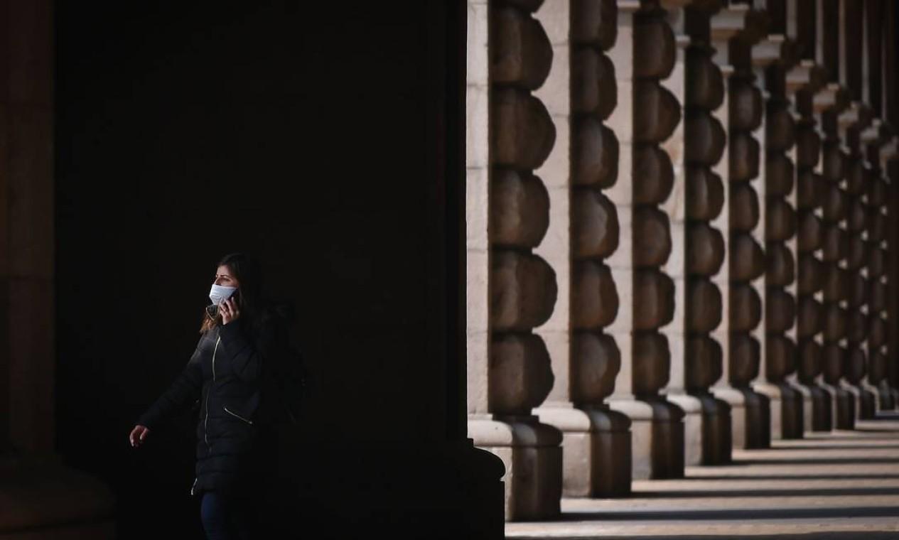 Uma mulher usa uma máscara protetora enquanto caminha no centro vazio de Sofia, depois que jardins públicos, parques infantis e instalações esportivas ao ar livre na Bulgária foram selados para impedir a reunião social Foto: NIKOLAY DOYCHINOV / AFP